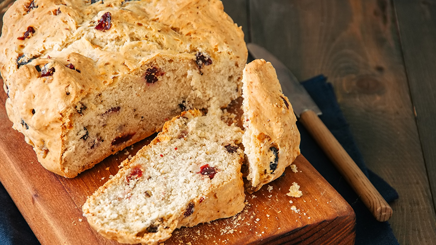 Image is of a loaf of bread with dried fruit in it.