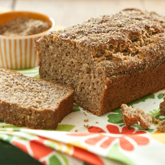 Banana bread with flax seed and honey on table.