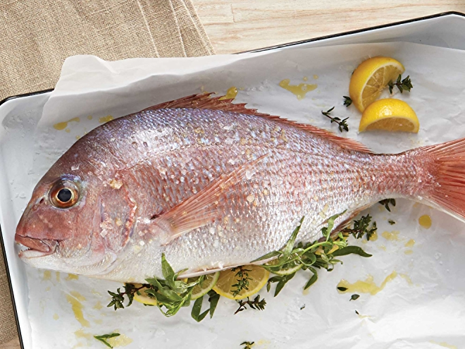 whole grilled fish on parchment with lemon and herbs
