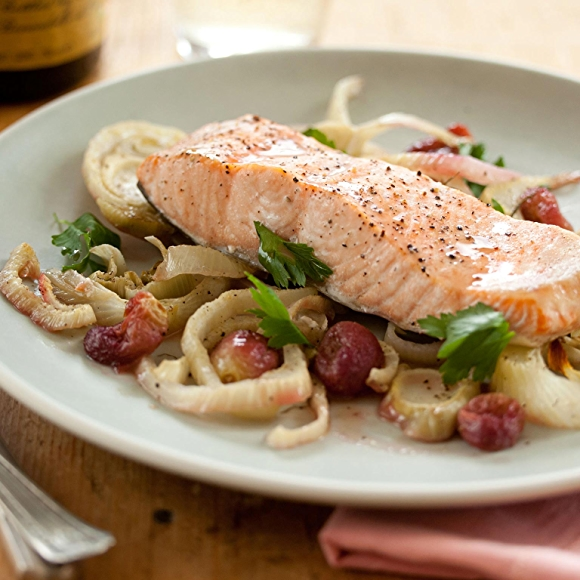 Roasted salmon and grapes on plate.