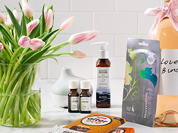 lifestyle image of tulips, wine, chocolate and oils for mother's day