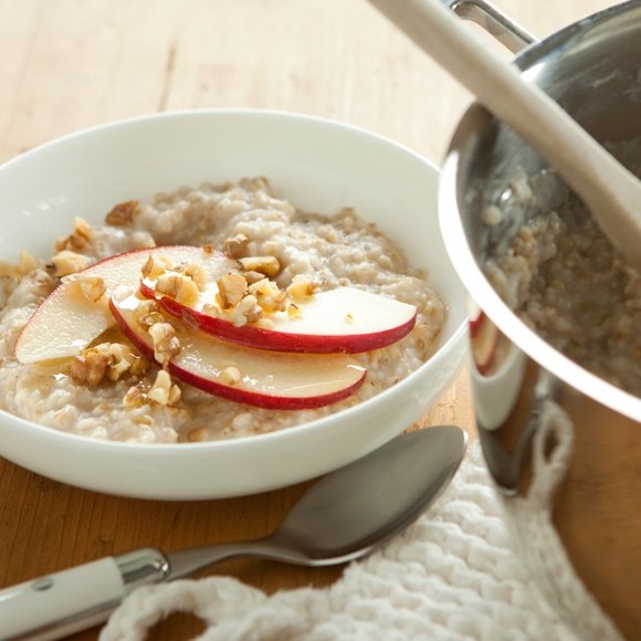 Oatmeal with sliced apple and nuts in bowl.