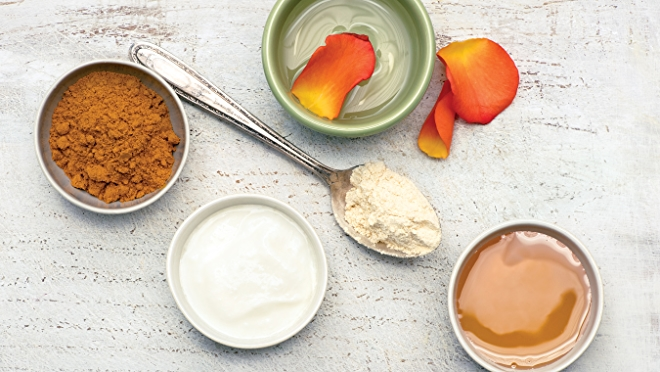 DIY facial mask and beauty products in bowls on white surface.