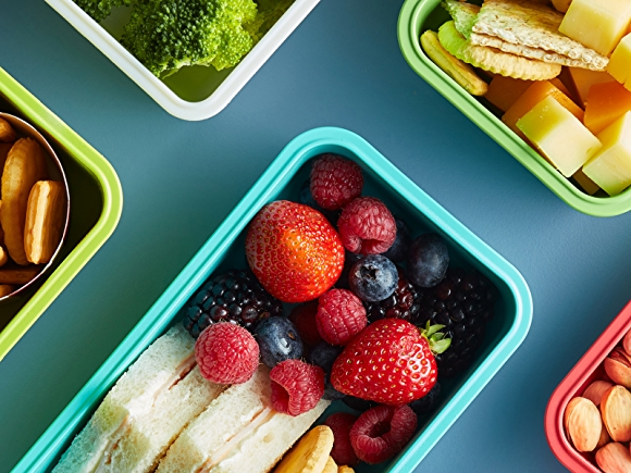 Bento boxes filled with healthy foods on blue background