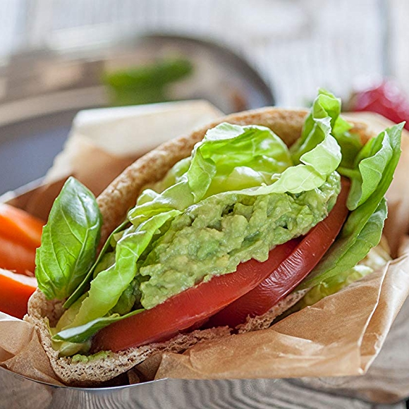 Pita pocket with avocado, tomato and lettuce with a side of carrots.
