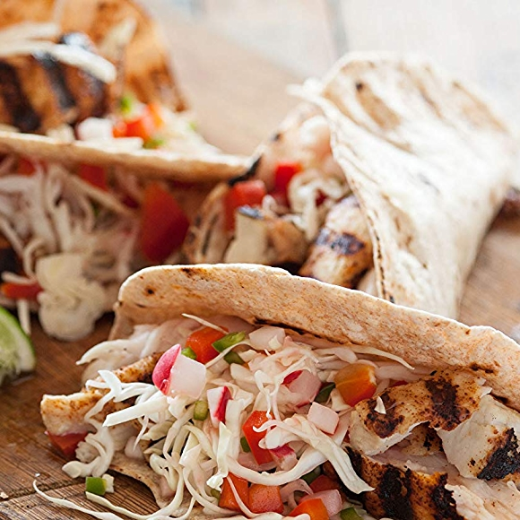 Recipe image of grilled paiche tacos with picked veggies, garnished with limes.