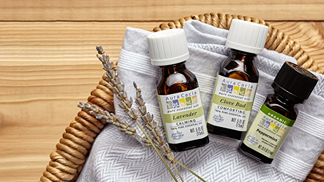 Essential oil bottles in basket on wooden surface.