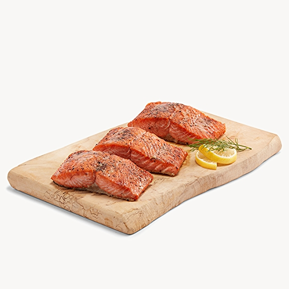 3 salmon fillets on a cutting board