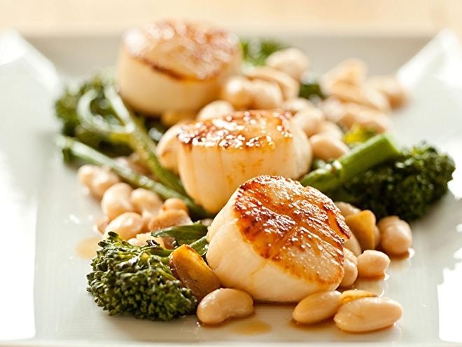 Recipe of seared scallops with broccoli rabe and white beans on plate.