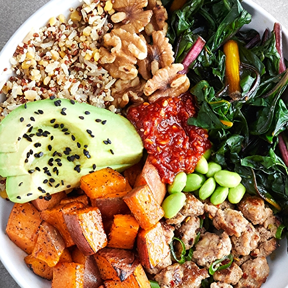 Bowl filled with turkey, chard, sweet potatoes, avocado and quinoa