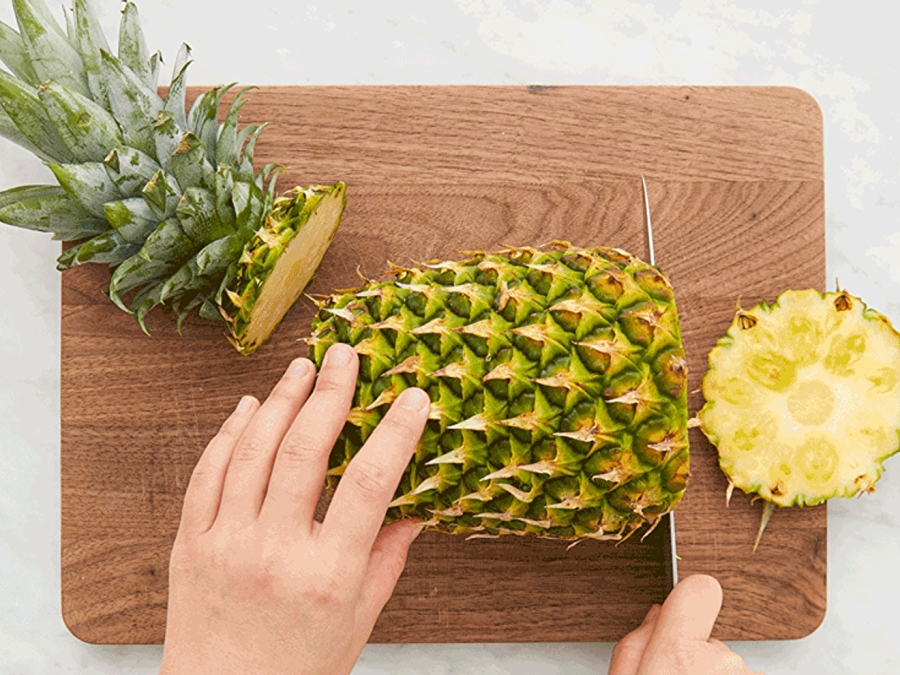 hands cutting pineapple on wooden cutting board
