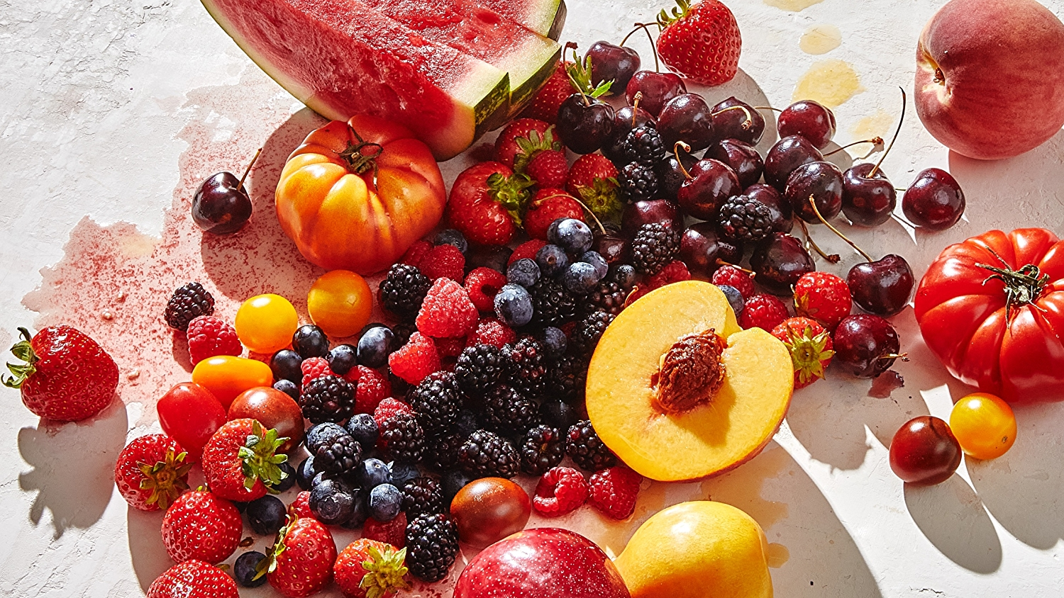 group of summer fruit: strawberries, peaches, blueberries, raspberries, blackberries, tomatoes and cherries