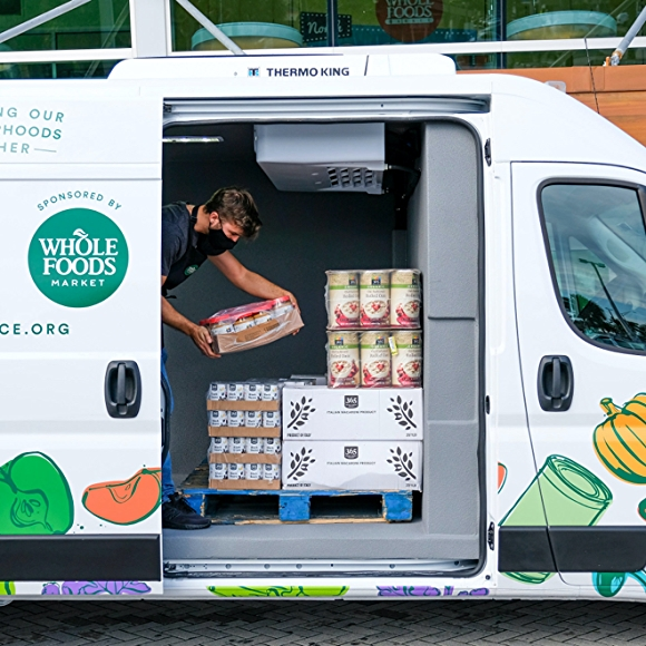 man loading van with whole foods products for nourishing our neighborhoods program