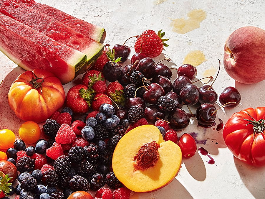 group of summer produce: tomatoes, watermelon, berries, peaches