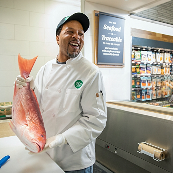 man from whole foods seafood department holding fish