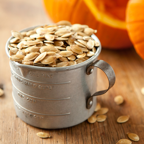 Roasted pumpkin seeds in tin measuring cup.