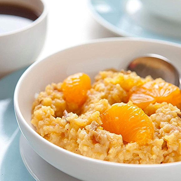 Image of Millet breakfast cereal with mandarin oranges in a bowl with a cup of coffee.