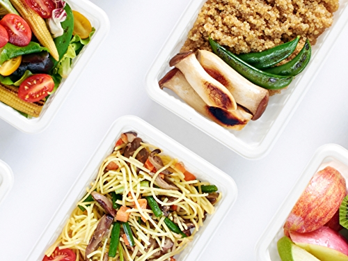 Vegan meal prep items in containers including apples, kiwi, noodles, vegetables and more