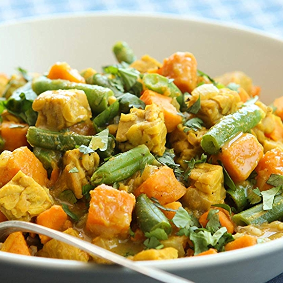Bowls of tempeh curry with sweet potatoes and green beans recipe.