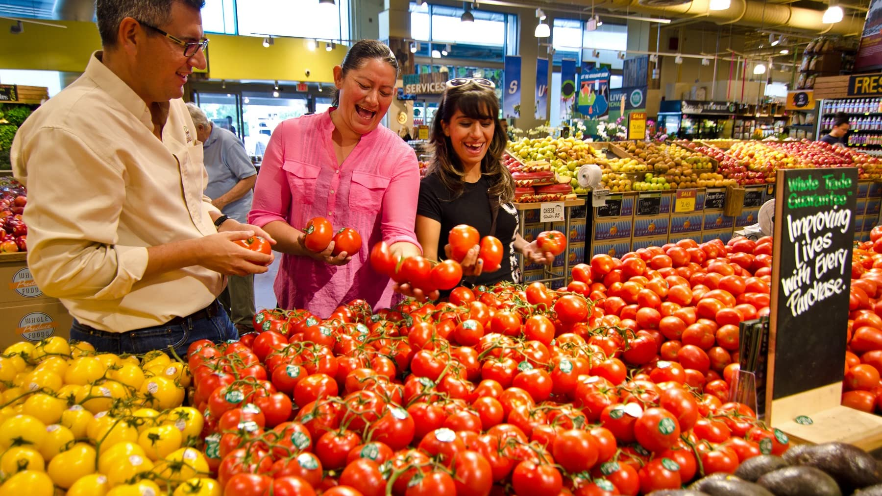 Olga (center) and Rosa Maria (right) examine Whole Trade® produce in a store.