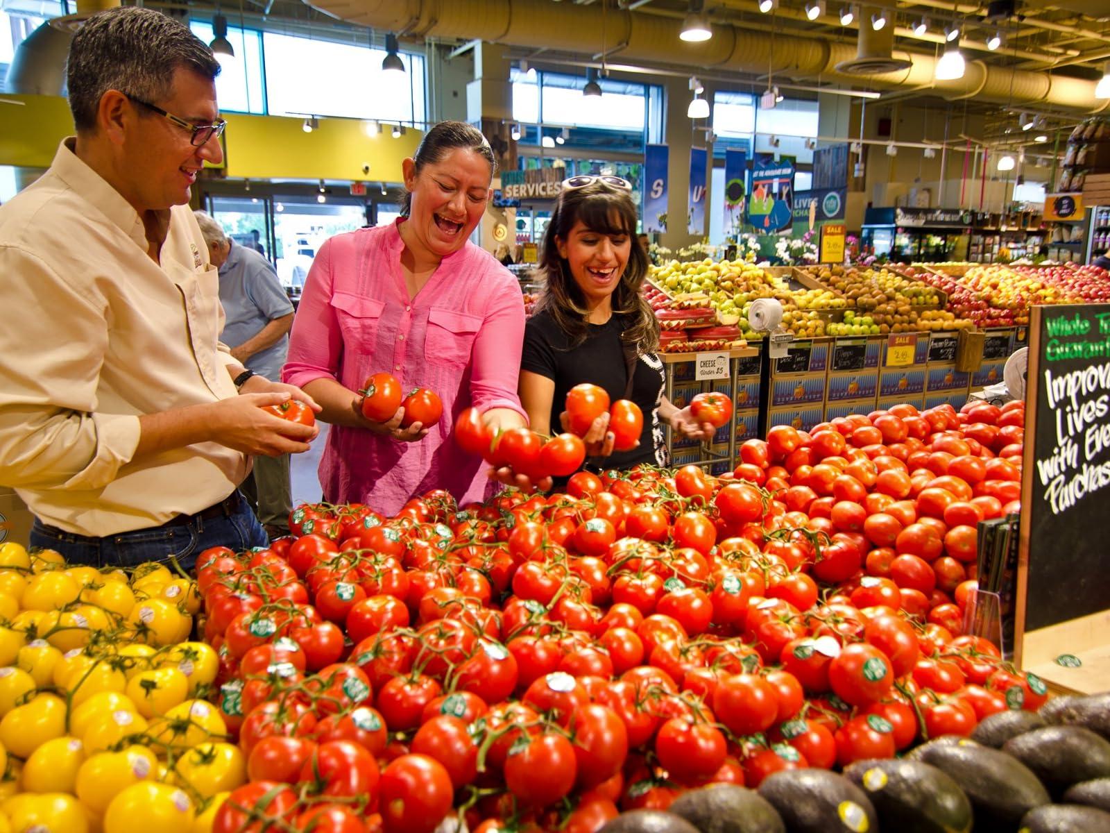 Olga (center) and Rosa Maria (right) examine Whole Trade® produce in a store.