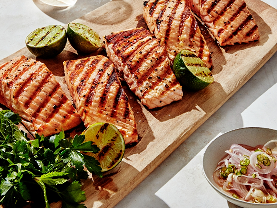 grilled salmon on wooden plank with fresh herbs salad