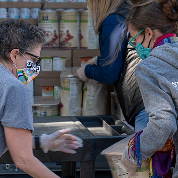 people volunteering with canned food