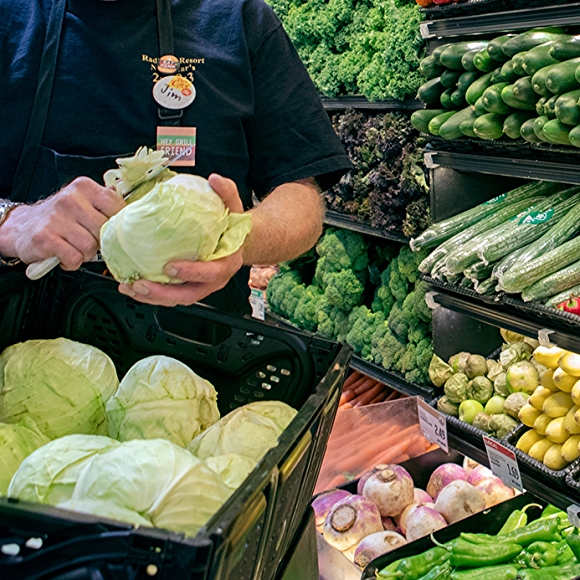 whole foods market team member with cabbage in produce department