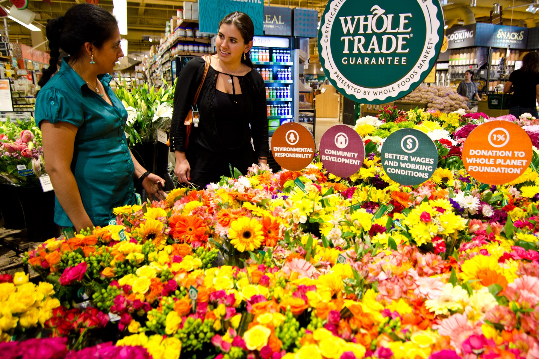 Lucia (left) and her co-worker Gabi (right) get to see how Whole Trade® flowers are displayed in the store.