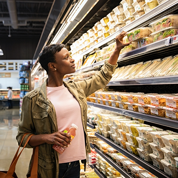 woman grabbing a pre-made sandwich from prepared foods department at whole foods