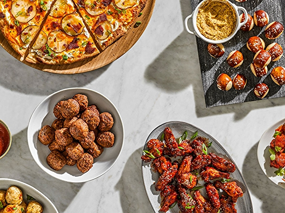 Pictured from left to right: Pizza, pretzle balls and mustard, wings, vegan meatballs, marinara sauce, plated and shot overhead.