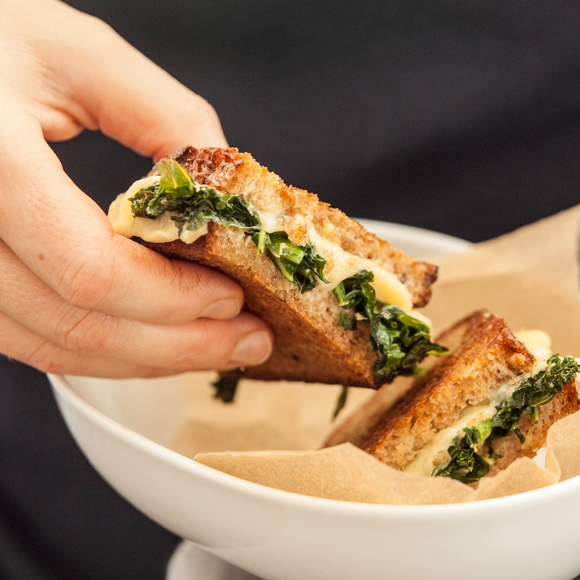 Grilled cheese and greens sandwich in bowl.