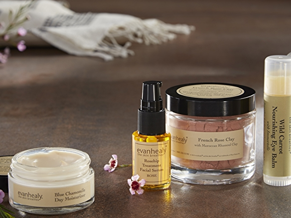 Evanhealy beauty and body care products on grey surface.