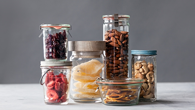 Nut and dried fruit snacks in jars on white surface.