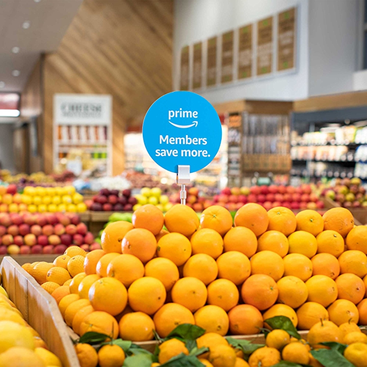 Prime members save more sign, among a display of oranges in the produce aisle.