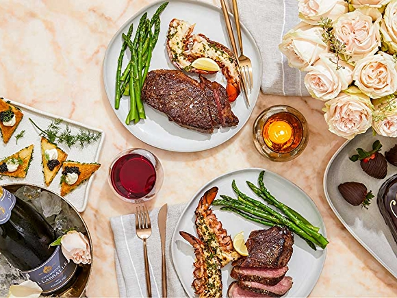 Valentine's Dinner shot overhead champagne, caviar, surf and turf, roses, chocolate covered strawberries, and heart-shaped cake pictured left to right