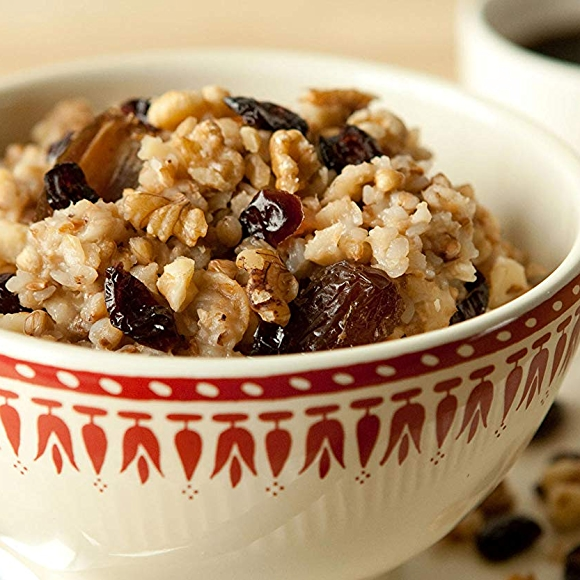 Apple oatmeal with buckwheat recipe in a bowl with a cup of coffee.