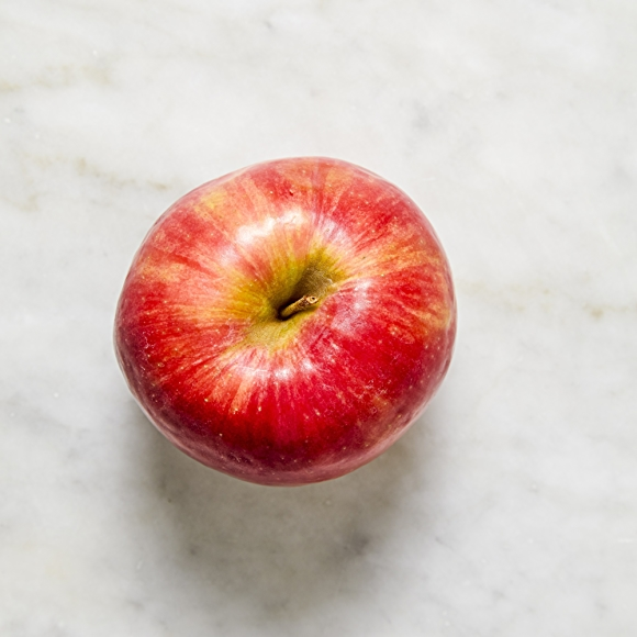 Photo of pink lady apple on white surface