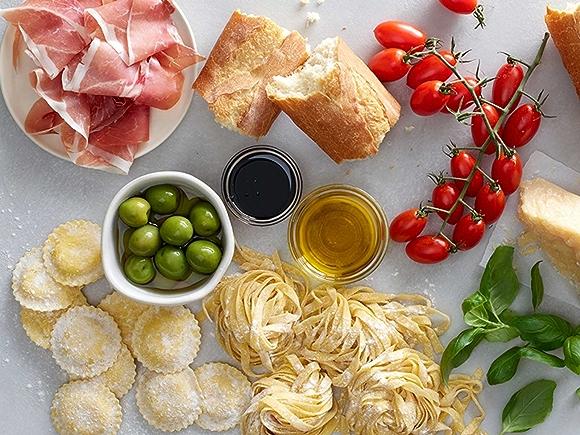 Italian ingredients shot overhead, prosciutto, bread, cherry tomatoes, parmesan, fresh pasta, olives
