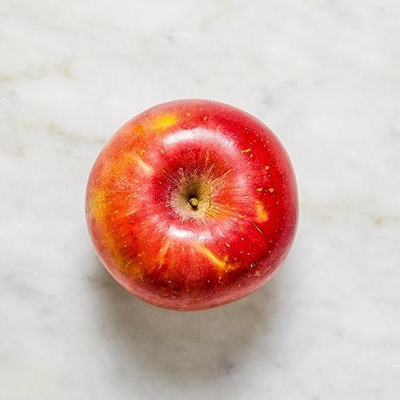 Photo of fuji apple on white surface