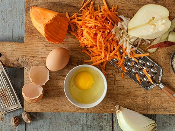 Image of cooking prep, including grated sweet potato, cracked egg and garlic.