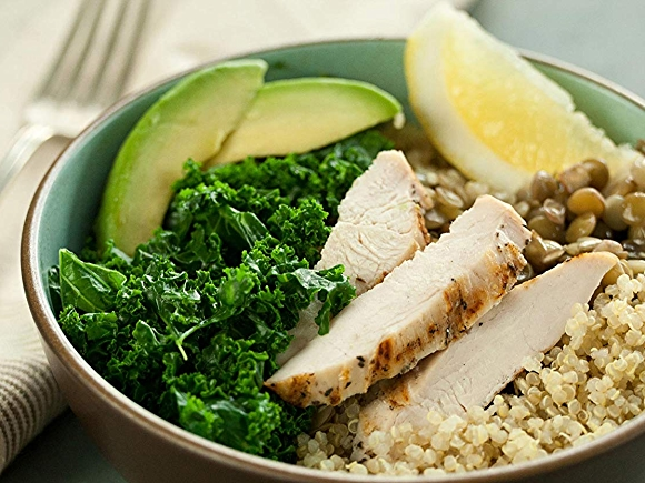 Image of protein bowl with quinoa, chicken, avocado, kale and lentils, garnished with lemon.