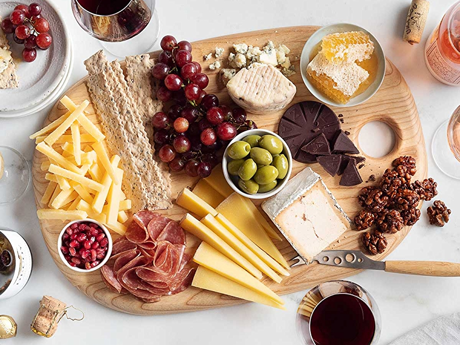 Fall cheeseboard with charcuterie, cheese, olives, grapes, and glasses of wine shot overhead