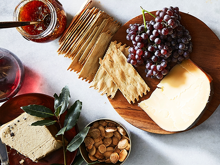 Cheeseboard with grapes, jam, and crackers