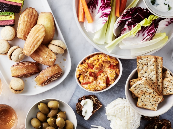 Table with crackers, cheese, cookies, olives, vegetables.