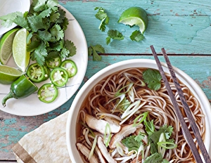 Overhead shot of bowl with Spicy Shiitake Pho recipe, with a side of limes, cilantro and jalapeño.