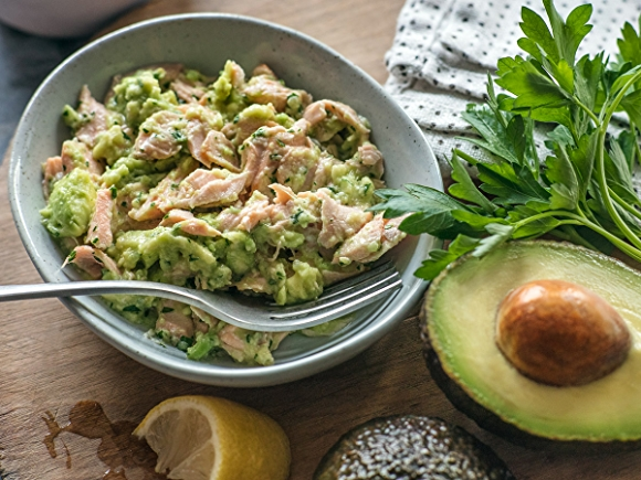 Salmon salad with avocado in bowl on table.