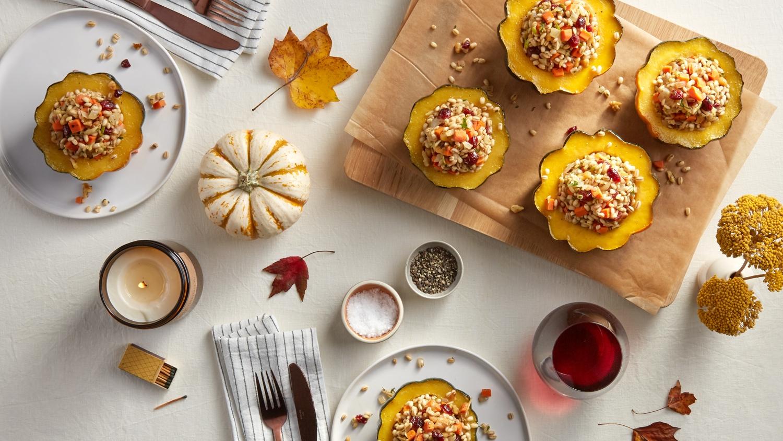 Stuffed acorn squash on fall themed table.