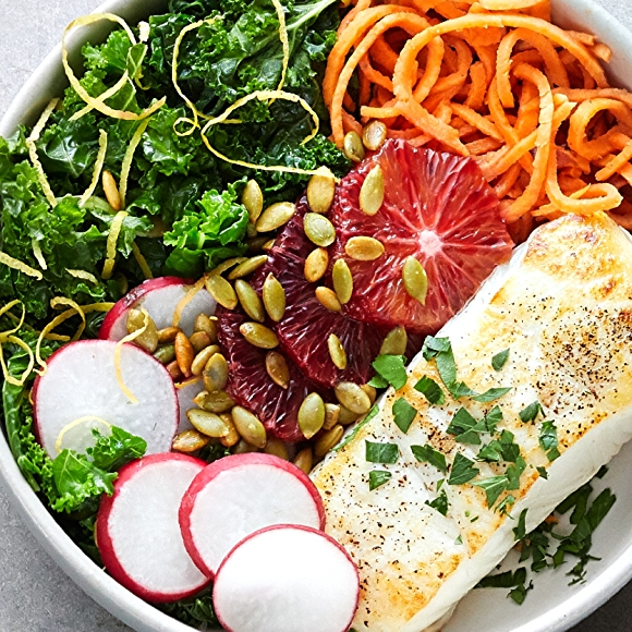 Bowl filled with halibut, sweet potato noodles, kale, carrots and radishes