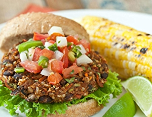 Image of southwest veggie burger topped with pico de gallo and a side of corn on the cob.